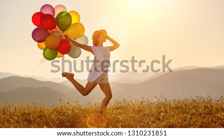 young happy woman with balloons at sunset in summer #1310231851
