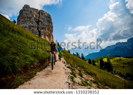 Couple cycling in Cortina d'Ampezzo, stunning Cinque Torri and Tofana in background. Woman and man riding MTB trail. South Tyrol province of Italy, Dolomites. #1310238352