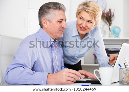 Mature man and woman watch interesting information on internet at ofice #1310244469