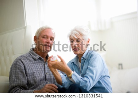 Mature adult couple reading the label of medicine while sitting on the floor. #1310331541