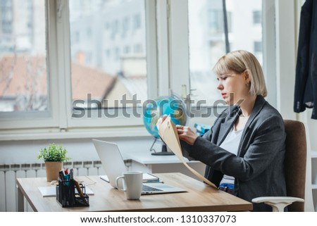 Young woman opening letter at her office #1310337073