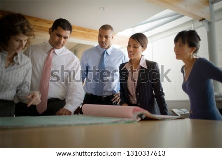 Business colleagues standing looking over plans in an office. #1310337613