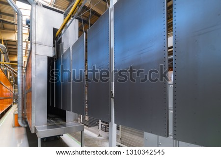 Powder coating line. Metal panels are suspended on an overhead conveyor line. Painting products in an electrostatic field. #1310342545