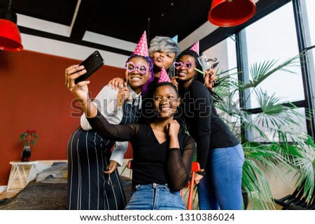 Happy african girls celebrate birthday in hats and take pictures on a smartphone