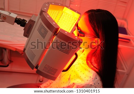 red light therapy. The girl goes through a course of skin rejuvenation with the help of red light treatment. #1310401915