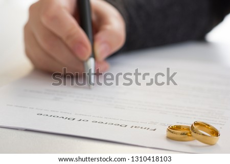 Hands of wife, husband signing decree of divorce, dissolution, canceling marriage, legal separation documents, filing divorce papers or premarital agreement prepared by lawyer. Wedding ring #1310418103