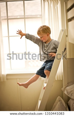 Little boy climbing down his bunk bed ladder