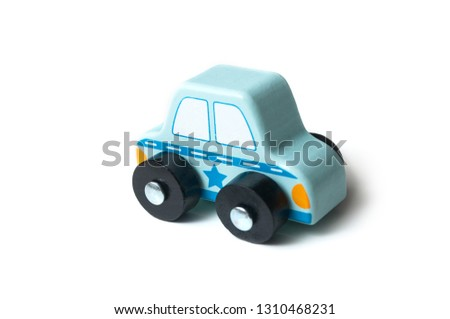 closeup of blue miniature wooden car on white background - concept police patrol