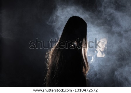 White Smoke Tan Skin Asian Woman black straight hair with mirror reflect herself face dark Background, Abstract high low exposure contrast, copy space for text logo, broken heart lonely girl can cry #1310472572