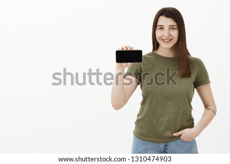 Portrait of friendly and happy young pleased positive brunette in casual t-shirt smiling and showing smartphone in horizontal position as presenting app or mobile phone over gray background #1310474903