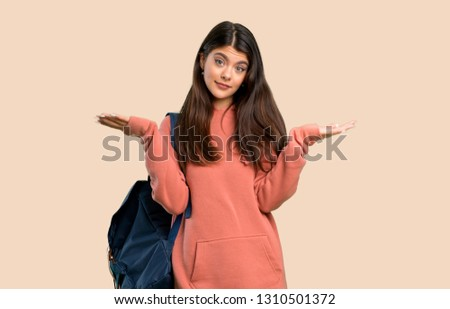 Teenager girl with sweatshirt and backpack having doubts while raising hands and shoulders on color background