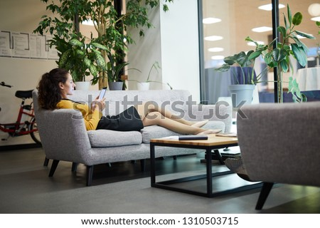Serious relaxed young lady lying on sofa in lobby and using digital tablet while reading online article #1310503715