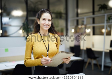 Smiling pretty young lady with badge on neck standing in modern open space office and holding sketchpad while looking at camera #1310504963