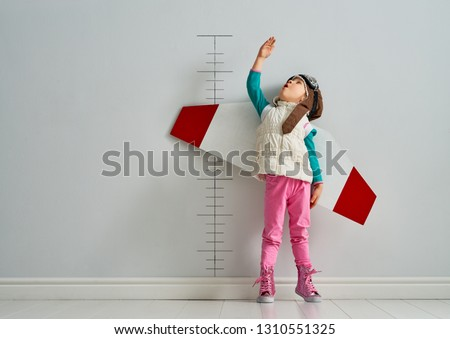 Little child is playing pilot. Kid is measuring the growth on the background of wall. #1310551325