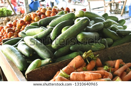 Cucumber tomatoes and carrots close up at traditional local market. #1310640965