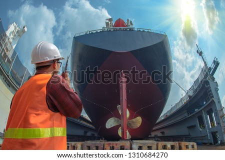supervisor, foreman, inspector, surveyor takes final inspection of the cleaning, repairing, recondition of over hull of the commercial ship in dry dock yard, ready to delivery the ship to the sea #1310684270