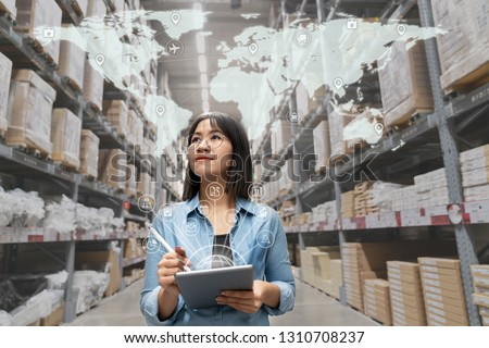 Portrait of happy young attractive asian entrepreneur woman looking at inventory in warehouse using smart tablet in management technology,  interconnected industry, asian small business sme concept. Royalty-Free Stock Photo #1310708237