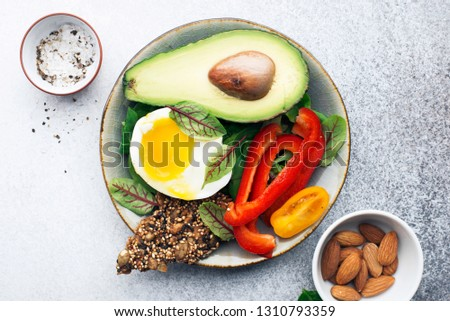 Keto bowl. Ketogenik diet snack. Cereal crackers without flour, paprika, avocado, eggs, spinach, nuts for a healthy diet. Top view #1310793359