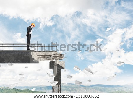 Young engineer in suit and helmet looking down while standing among flying paper planes on broken bridge with skyscape and nature view on background. 3D rendering. #1310800652