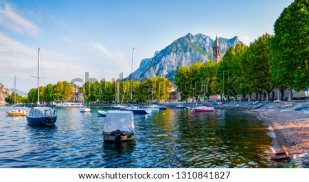 Blue waters of the Alpine lake are sparked in the first rays of the sun. Amazing summer scene of Como lake. Wonderful morning cityscape of central park of Lecco town, Italy, Europe.  #1310841827