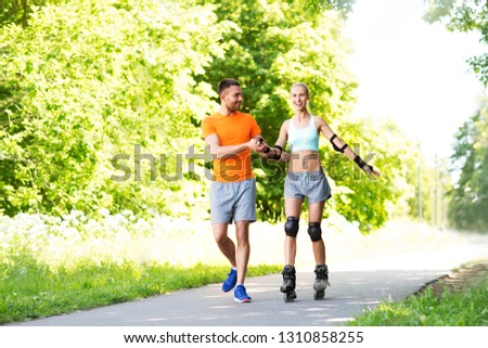 fitness, sport and healthy lifestyle concept - happy couple with roller skates riding outdoors in summer park #1310858255