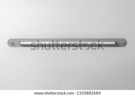 Beautiful metal gray LED lamp on the light wall background indoors. Closeup horizontal photo. #1310882684
