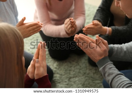 Group of people praying together indoors #1310949575