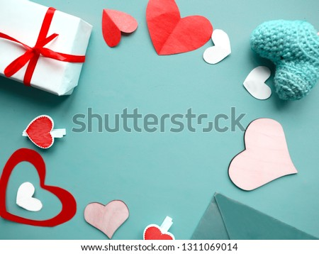 Valentines Day background. Hand made knit and wooden hearts and red giftboxes on blue background. Flat lay, top view, copy space #1311069014