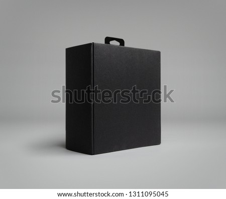 10 inches black box for luxury product packaging. Studio photo on gray background with shadow. The box has a black hanger. Isometric view, low angle photo #1311095045