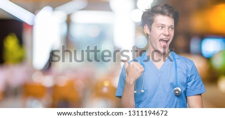 Young doctor wearing medical uniform over isolated background smiling with happy face looking and pointing to the side with thumb up. #1311194672