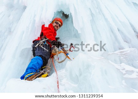 ice climber on a vertical wall of a frozen waterfall among huge icicles #1311239354