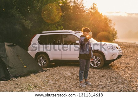 woman taking picture of sunrise on her phone. car camping. lifestyle concept