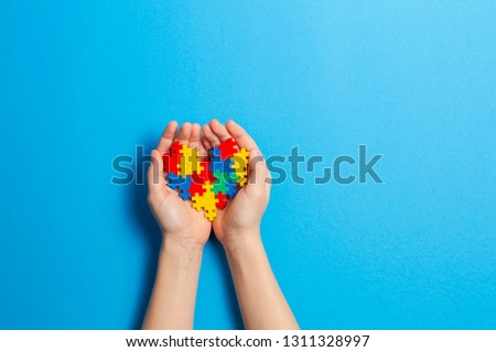 Child hand holding colorful heart on blue background. World autism awareness day concept