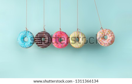 Newton's cradle from doughnuts. Collision balls made from donuts. Harm of sugar, donuts time or healthy diet concept. Dependence on flavoring, diabetes problems, weight loss. #1311366134