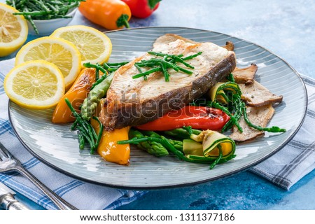 Grilled halibut steak with vegetables - sweet mini peppers, courgette, asparagus and oyster mushrooms, garnished with samphire