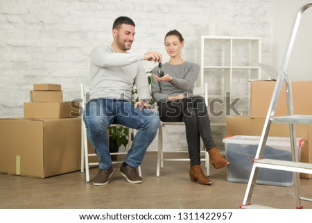 Loving couple sitting on the floor in their new house, smiling and looking at a key of their new property #1311422957