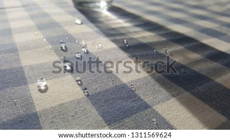 drops of water on a checkered tablecloth #1311569624