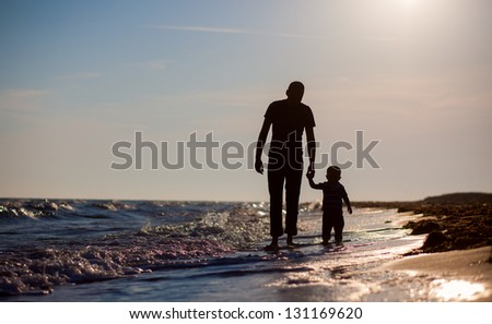 father and son to the sea at sunset #131169620