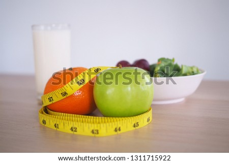 Tape measure around the green apple and orange. Next there are milk and vegetable salad on the wooden table. Eating for good health and weight loss. Diet concept   #1311715922