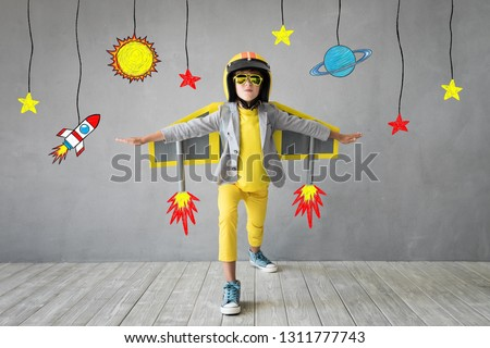 Happy child playing with toy jet pack. Kid pilot ready to fly. Success, innovation and leader concept #1311777743