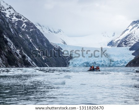 The toe of the Garibaldi Glacier melts into its ice-filled fjord between rugged snow-clad mountains of Chilean Patagonia. Royalty-Free Stock Photo #1311820670