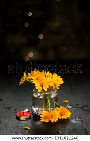 Yellow flowers in a glass vase near to  candle #1311821240