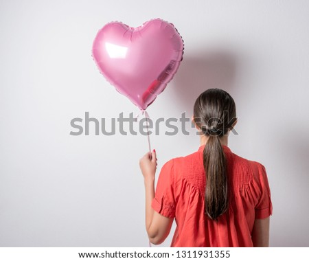 Beautiful young woman with a heart shaped balloon on a bright background. Valentine's day concept. #1311931355