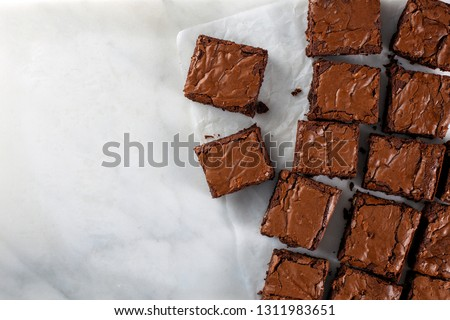 Chocolate brownie on paper on white marble top view flat lay looking down with text space on left copy space #1311983651