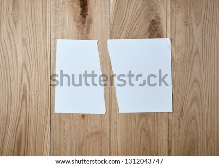 half torn blank white sheet  on a  wooden background, close up #1312043747