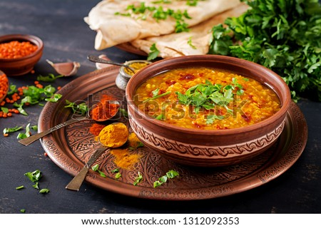 Indian dal. Traditional Indian soup lentils.  Indian Dhal spicy curry in bowl, spices, herbs, rustic black wooden background. Authentic Indian dish. Overhead #1312092353