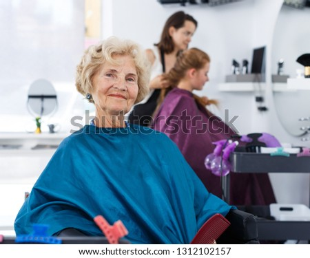 Elegant senior woman in hairdressing cape sitting in barber chair, waiting for haircutting