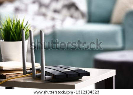 Modern wi-fi router on light table in room #1312134323