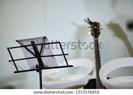 Royalty high quality free stock photo of music stand with microphone and guitar in blurred background