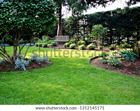 A beautiful view of manicured formal garden landscape design with green lawn and planted areas including park bench  #1312145171